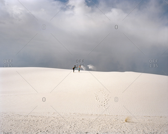 Two women playing with sand in the desert in White Sands, New Mexico