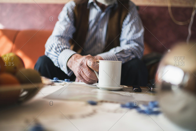 Hand of man grabbing cup of coffee