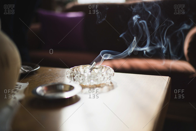 Smoking cigarette in ashtray on table