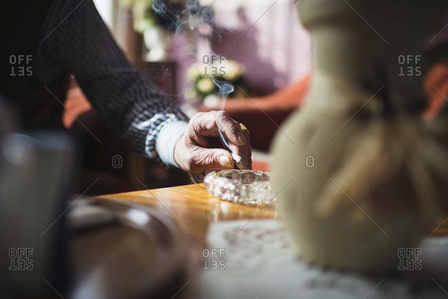 Hand of senior man knocking cigarette in ashtray