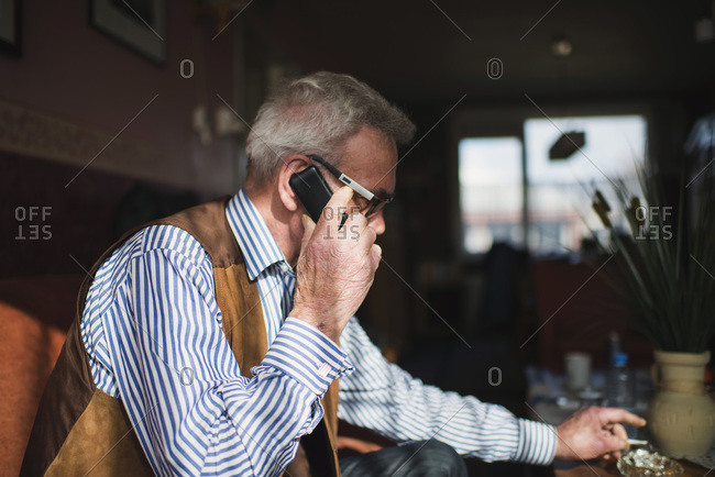 Senior man with cell phone knocking cigarette in ashtray