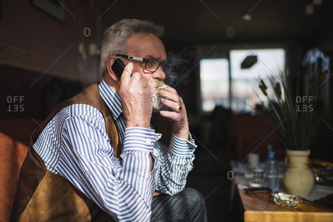 Smoking senior man calling with cell phone at home