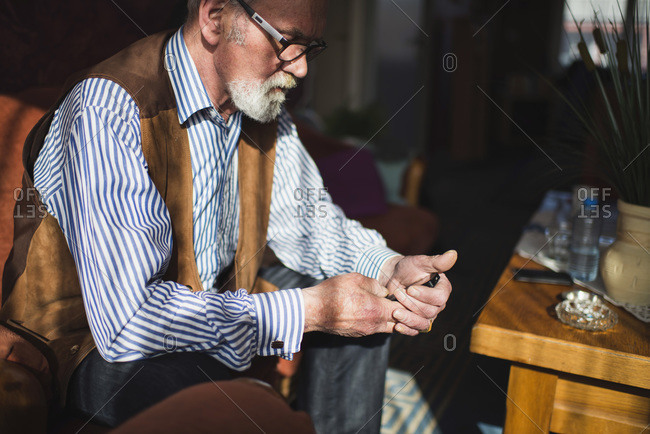 Senior man texting with cell phone at home