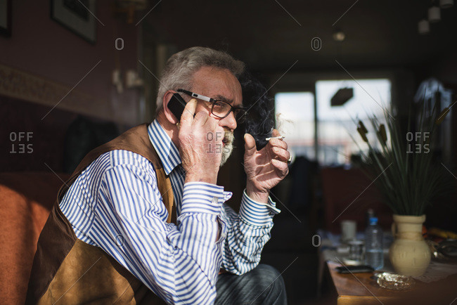 Senior man with cell phone and cigarette at home