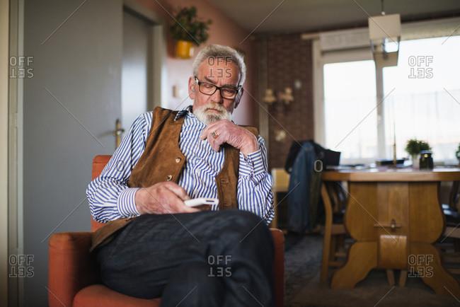 Elderly man operating television remote control