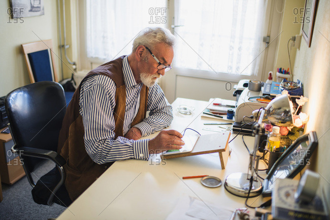 Elderly man at home using tablet