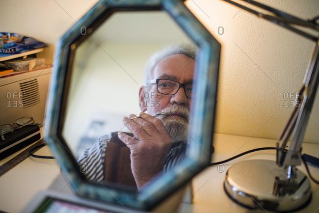 Senior man cutting beard in mirror