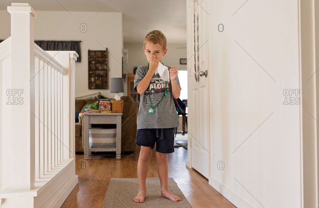 Young boy wiping nose with tissue