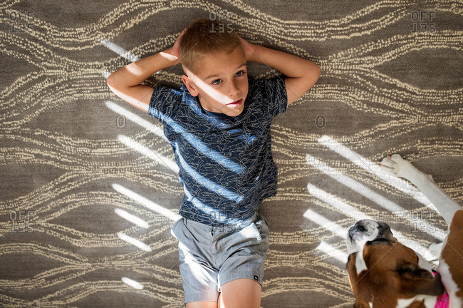 Overhead view of young boy lying on rug with dog