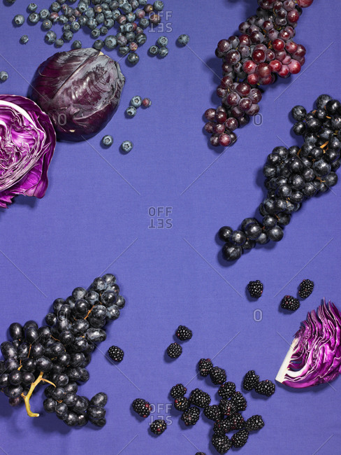 Grapes, blackberries, purple cabbage, and blueberries on a purple background