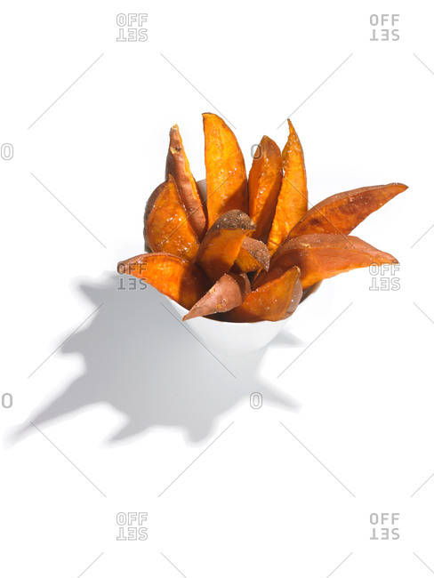 Sweet potato wedges in a cup on a white background