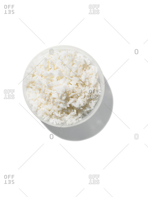 Overhead view of a bowl of white rice on a white background