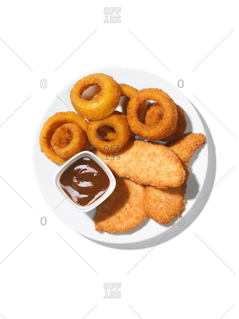 Overhead view of onion rings and fried fish filets on a white background