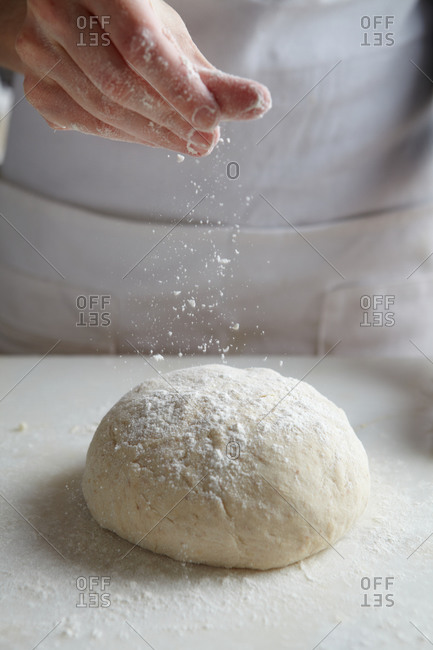 Baker dusting a dough ball with flour