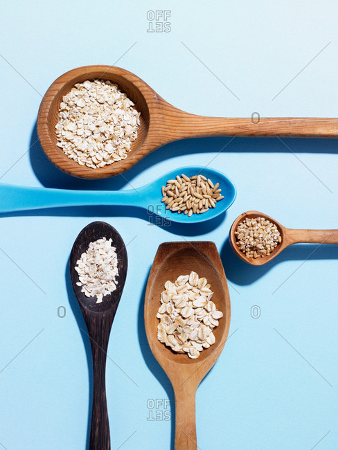 Overhead view of wood spoons filled with grains and oats