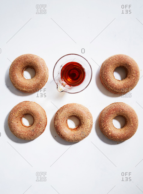 Overhead view of donuts and a cup of maple syrup
