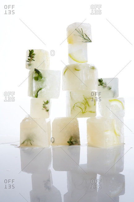 Ice cubes filled with citrus and herbs on a white background