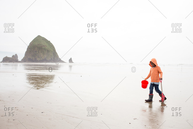 Boy playing on the beach by Haystack Rock, Oregon