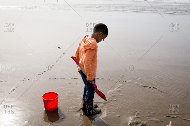 Boy playing on the beach with bucket and shovel