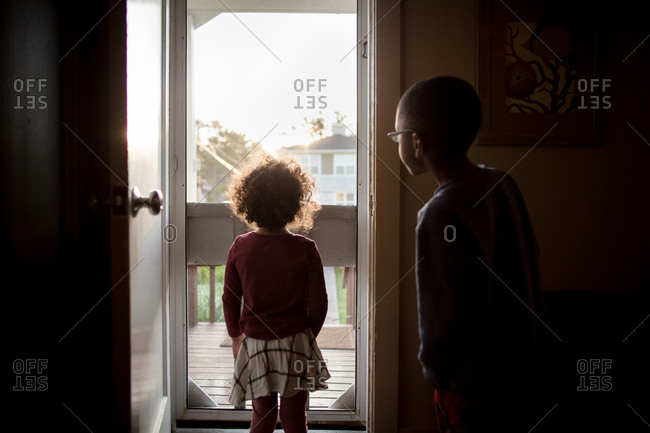 Little girl and boy looking out the front screen door