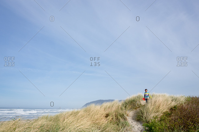 Boy walking with shovel on a grassy beach