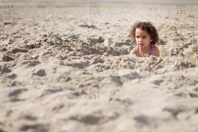 Girl sitting in a hole in the sand on a beach