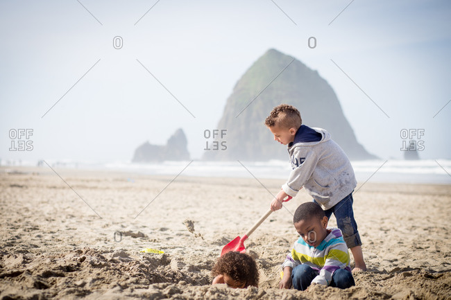 Brother burying sister in a hole on a beach