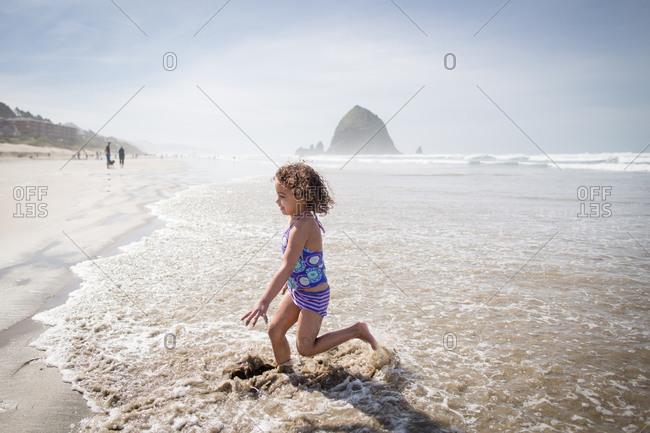 Girl running in waves by Haystack Rock, Oregon