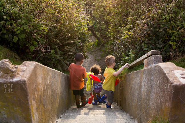 Siblings carrying toy shovels down a set of cement stairs
