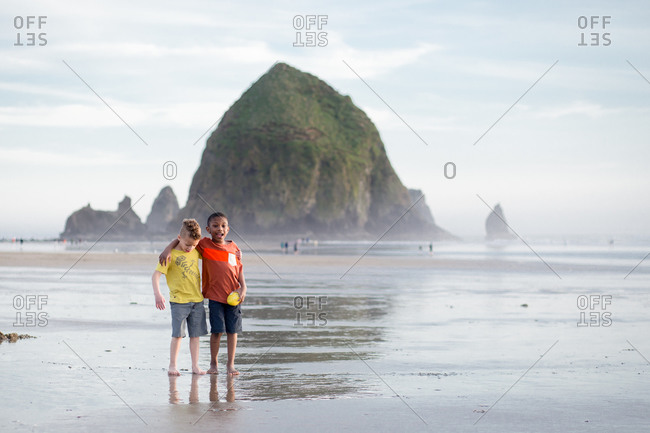 Brothers standing on the beach by Haystack Rock, Oregon