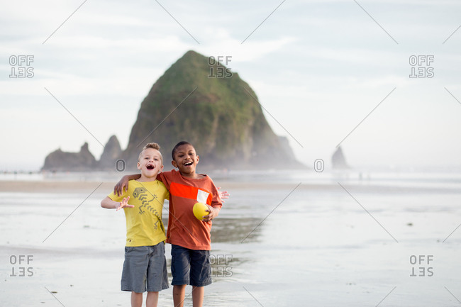 Brothers hugging on the beach by Haystack Rock, Oregon