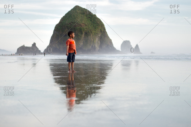 Boy standing in front of Haystack Rock, Oregon