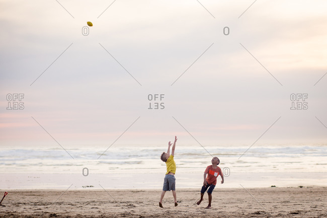 Brothers playing football on a beach