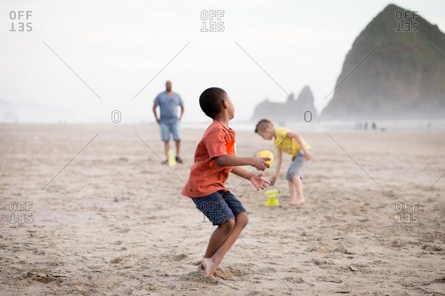 Boy throwing a ball on the beach by Haystack Rock, Oregon
