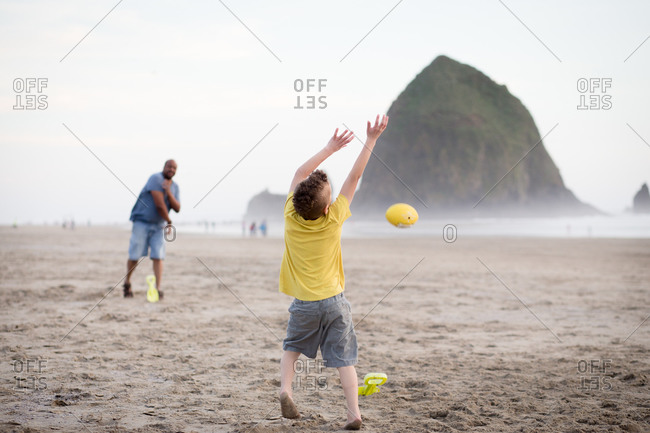 Boy catching a ball on the beach by Haystack Rock, Oregon