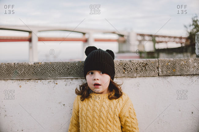 Young girl standing outside near a wall wearing a knit hat and sweater