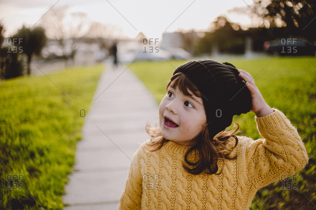 Young girl standing outside wearing a knit hat and sweater