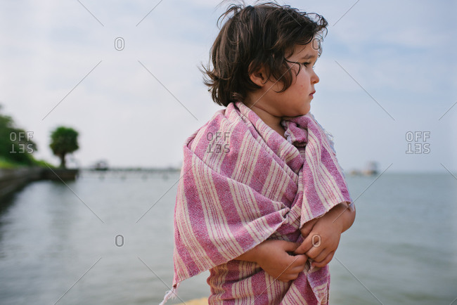 Toddler girl wrapped in a towel by sea