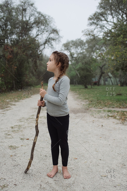 Young girl standing barefoot on dirt road with a stick