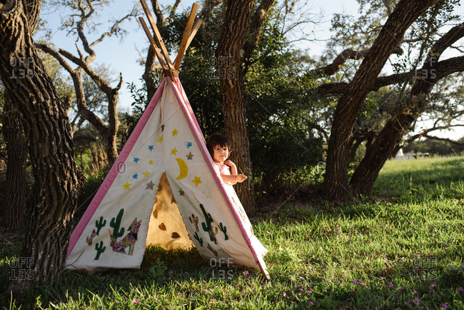 Toddler girl playing in tipi tent