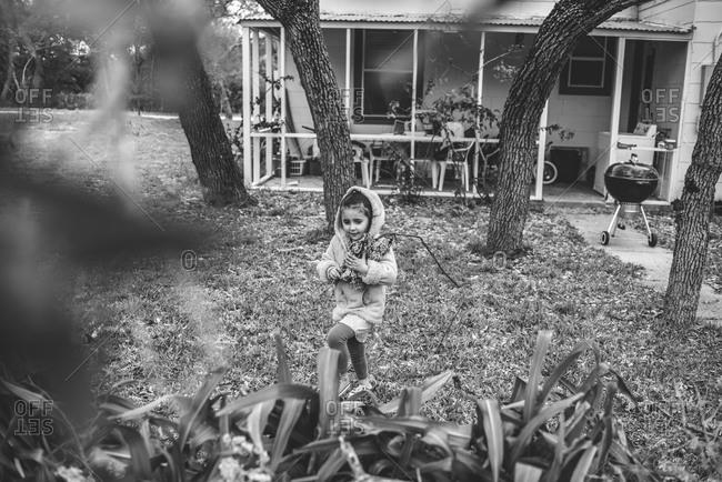 Young girl gathering wood in backyard