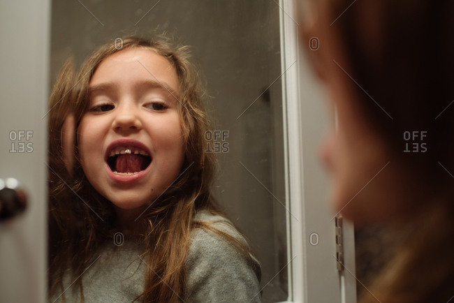 Young girl wiggles loose tooth with her tongue while looking in mirror