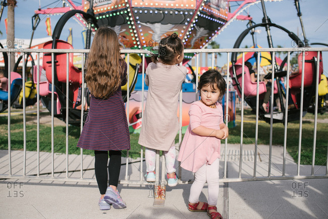 Three young children watch a spinning ride at carnival