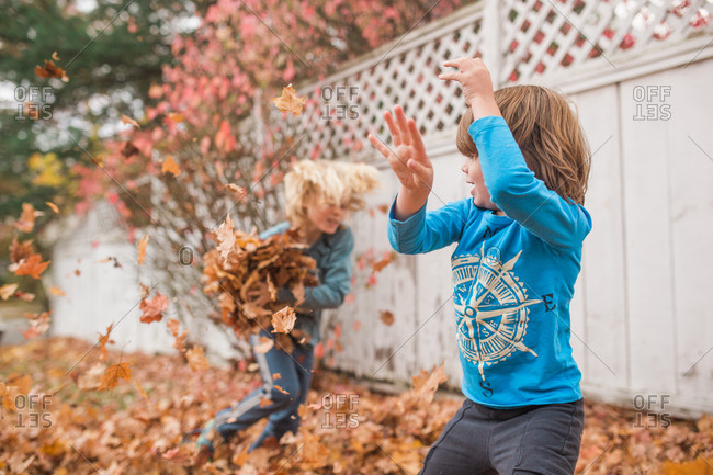Two boys playing outside in a yard full of autumn leaves