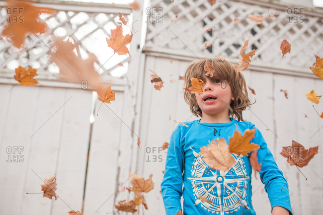 Boy standing outside in a flurry of falling leaves