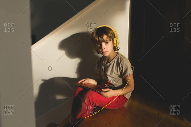 Young boy sitting on the stairs wearing headphones and holding a digital tablet