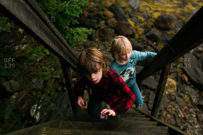 Two boys outside climbing a wood staircase together