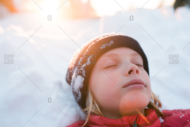 Close-up of a young girl lying down in the snow