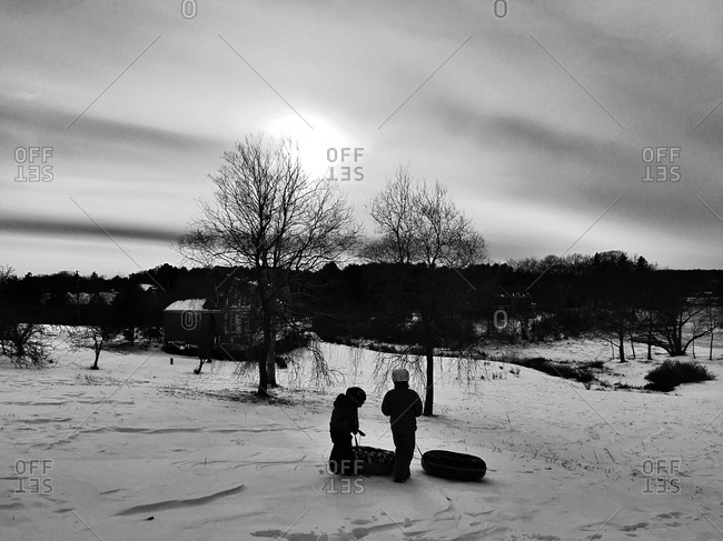 Silhouette of two children sledding in a snowy field