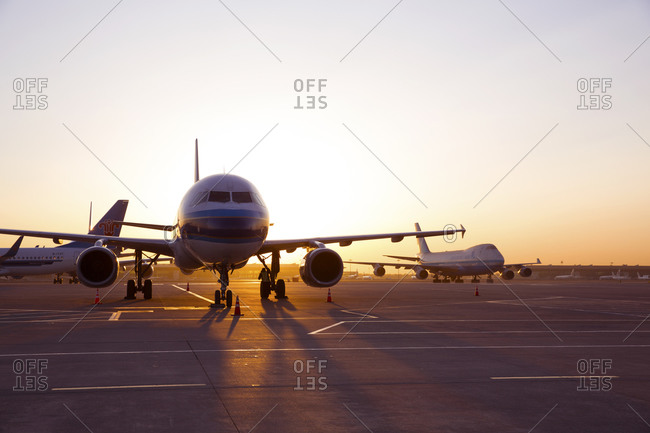 Shanghai, China - March 25, 2016: Airplanes sitting on a tarmac at sunset in Shanghai, China